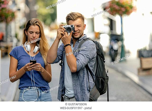 Netherlands, Maastricht, young couple exploring the city taking pictures