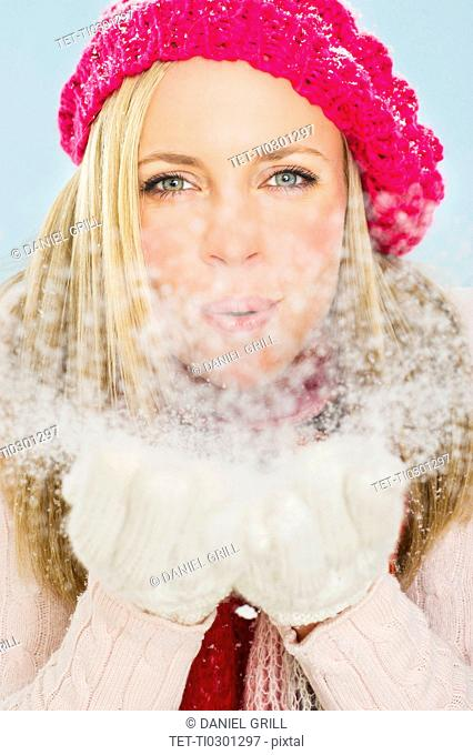Studio portrait of young woman blowing snow