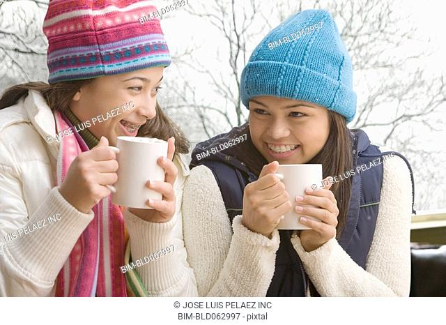 Multi-ethnic girls in snow drinking hot cocoa