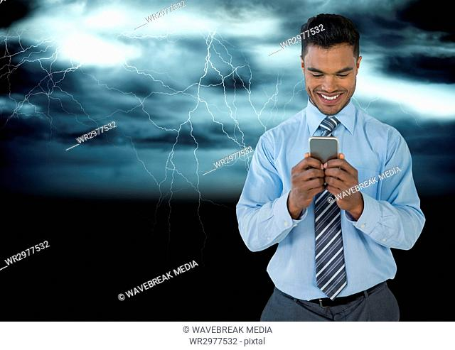 Smiling man texting in darkness with lightenings