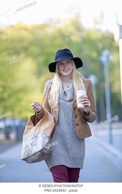 Pretty blonde woman with hat and coffee to go walking in City Center