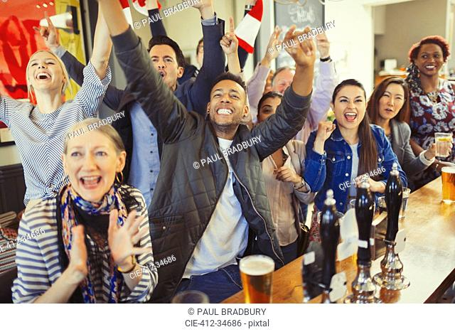 Enthusiastic sports fans cheering and watching game at bar