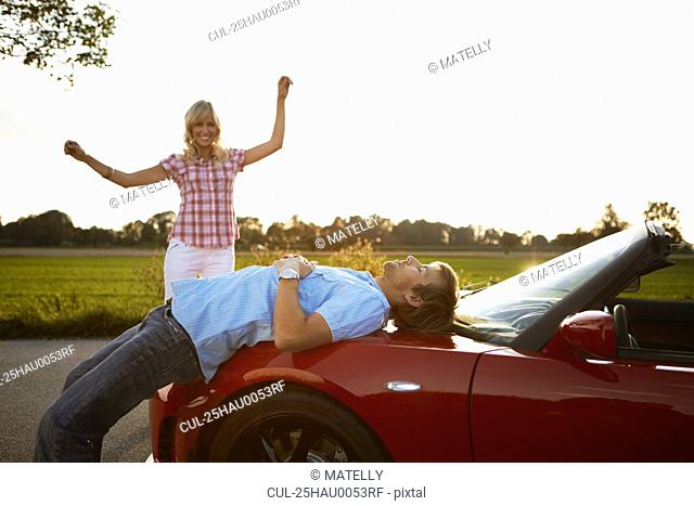 Couple relaxing in nature around a car