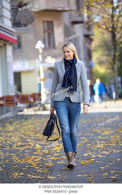 Pretty elegant woman walking with handbag in citycenter