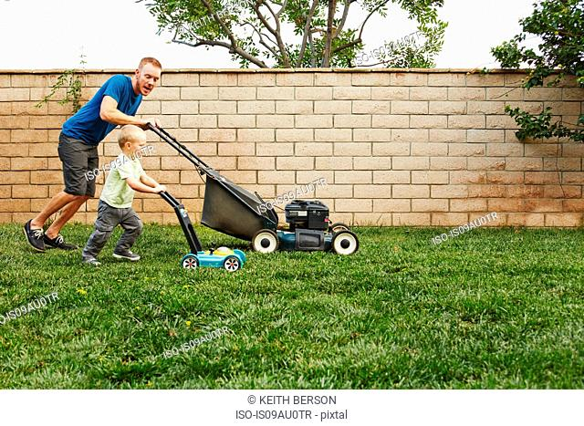 Father and son mowing lawn in backyard