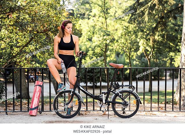 Fit young woman with bicycle, leaning on railing in a park