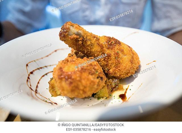 two breaded chicken leg in white deep plate on a table in restaurant