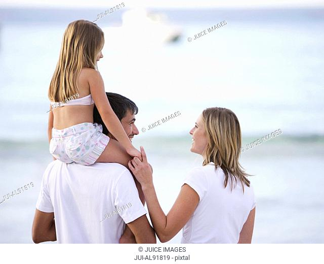 Family smiling at each other at beach