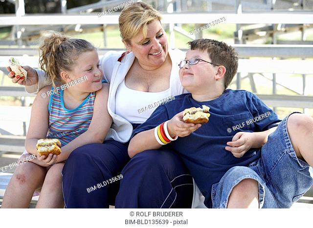 Mother and children eating sandwiches on bleachers