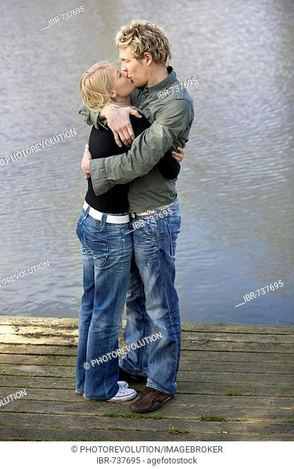 Couple hugging and kissing on a wooden dock