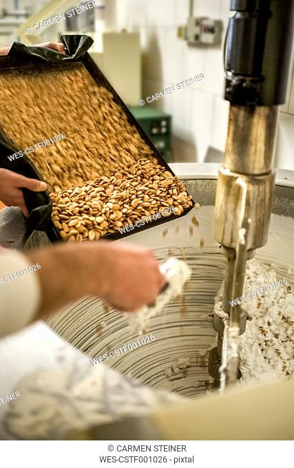 Italy, Manufacturing of traditional torrone in confectionery, putting almonds in the mixer