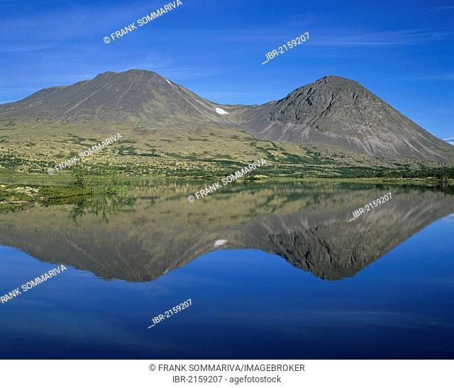 Twin peaks of the mountain group Stygghøin, reflected in Lake Dørålstjørnin, Rondane National Park, Norway, Scandinavia, Europe