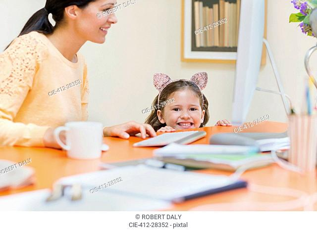 Portrait smiling girl in mouse ears headband with mother at computer