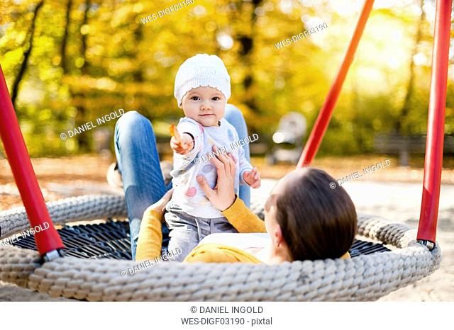 Portrait of baby girl relaxing with her mother on a swing in autumn