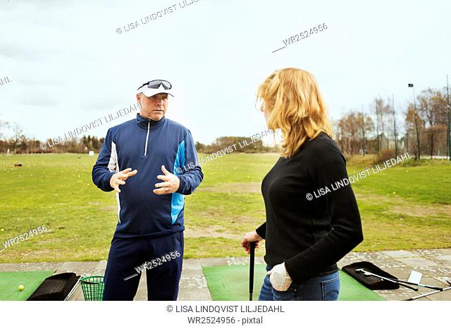Man talking with woman while standing at driving range