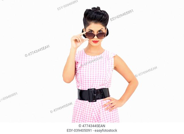Pretty black hair model looking over her sunglasses on white background