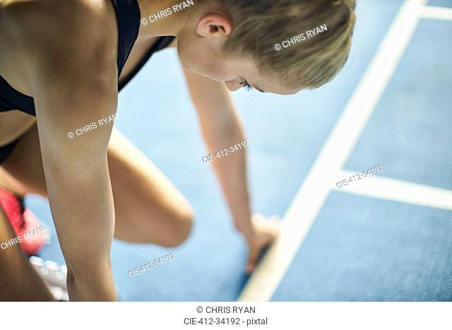 Focused female runner ready at starting block on sports track