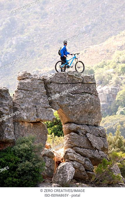 Young man standing on rock formation with mountain bike