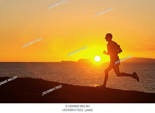 Man jogging along shore at sunrise/sunset