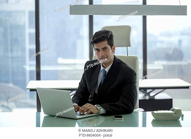India, Businessman at desk looking up from over laptop