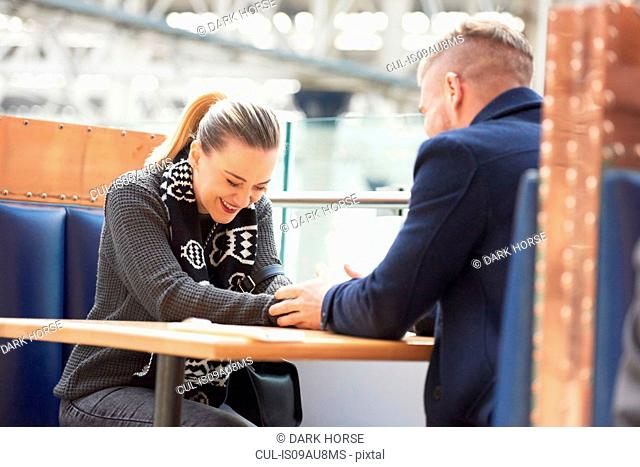 Young couple sitting at cafe, holding hands, laughing