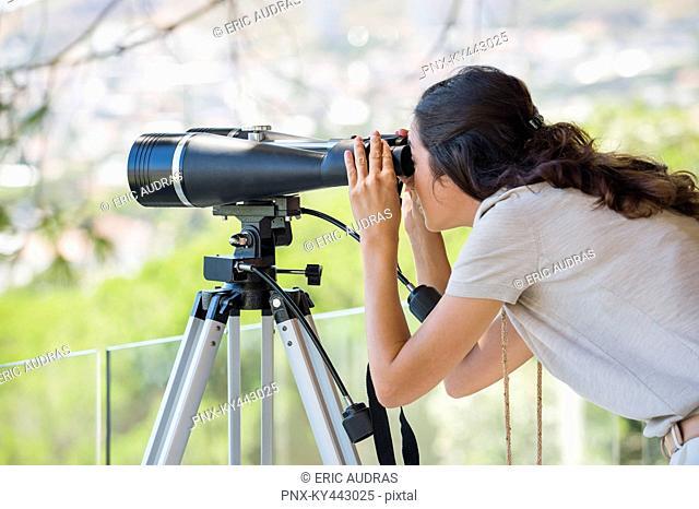 Woman looking through binoculars on tripod