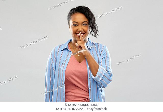 happy african american woman with finger on lips