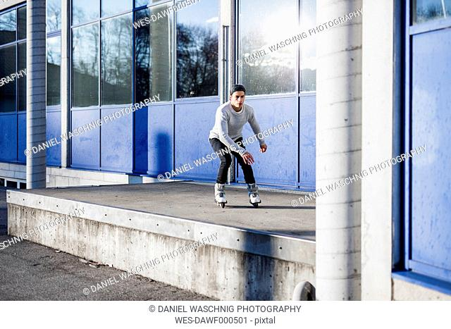 Young man inline skating along a building