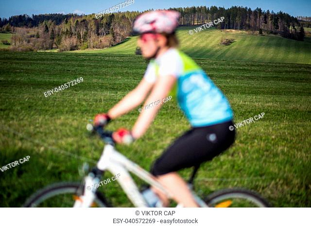 Female mountain biker out of focus with in focus landscape in the distance behind her
