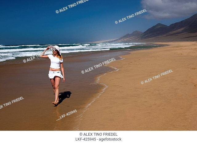 Young woman walking along the beach, Nature Reserve, Jandia, Fuerteventura, Canary Islands, Spain, Europe
