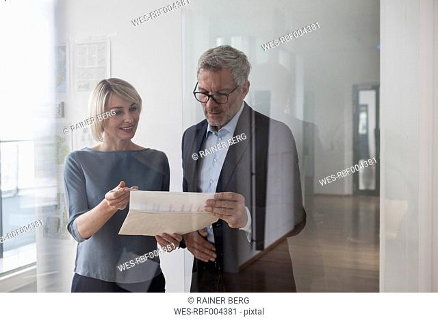 Businessman and woman working together in office discussing documents