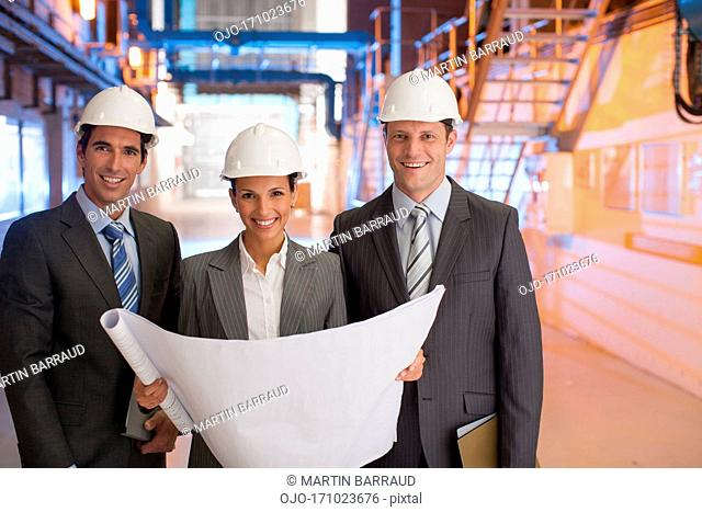 Business people reviewing blueprints in factory