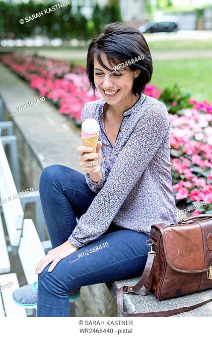 Smiling woman sitting on bench and eating ice cream