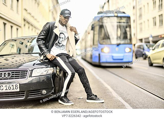young man sitting on car at city street next to tram, wearing casual fashion, in Munich, Germany