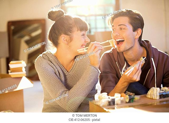 Couple eating sushi together in new home
