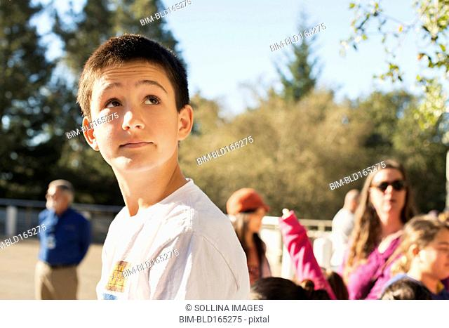 Caucasian student looking up on field trip