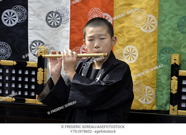 Little japanese boy playing the flute for the Takayama festival, Japan, Asia