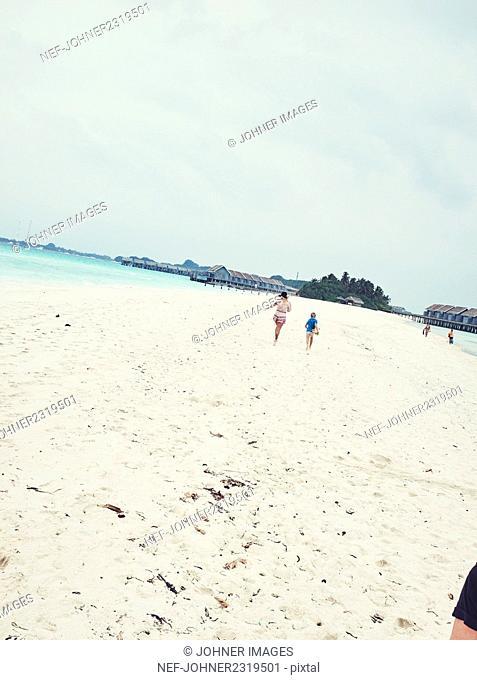 People running on sandy beach