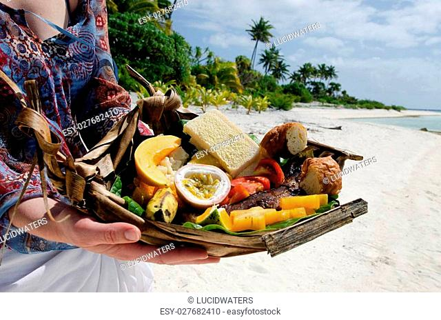 Young woman hands carry tropical food of grilled fish, fruits and vegetables dish served on deserted tropical island in Aitutaki lagoon, Cook Islands