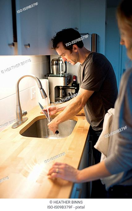 Mid adult couple washing kitchen knife at kitchen sink