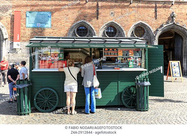 Bruges, Belgium - July 7, 2017: Tourists in front of a stand selling french fries in the market square in the center of Bruges
