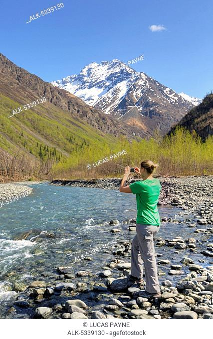 Female hiker photographing the East Fork Eklutna River and Chugach Mountains with a smart phone, Chugach State Park, Southcentral Alaska, Spring, HDR