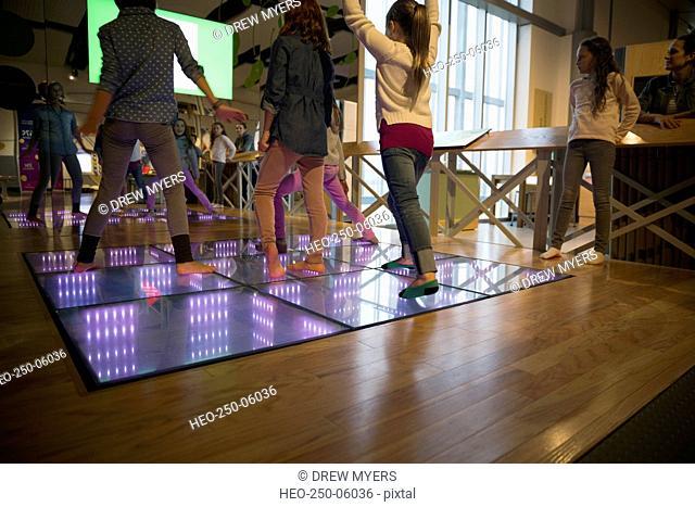 Girls dancing on illuminated floor at science center