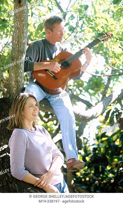man with guitar serranaiding a woman