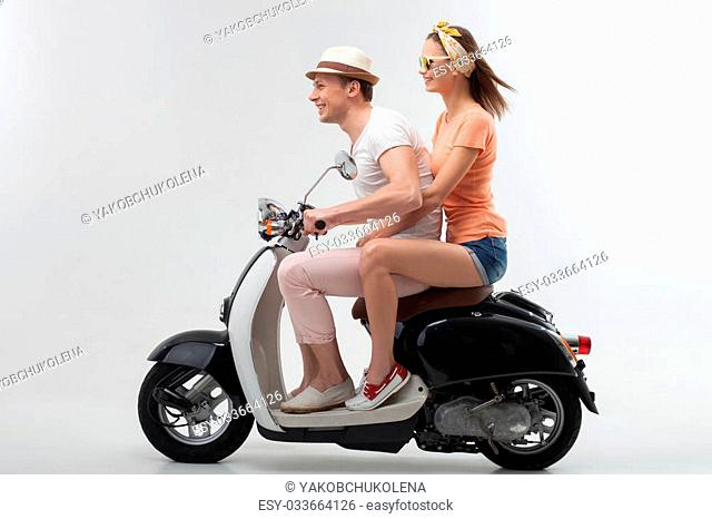 Full length portrait of beautiful man and woman traveling by scooter. They are sitting and looking forward with happiness. The lovers are smiling