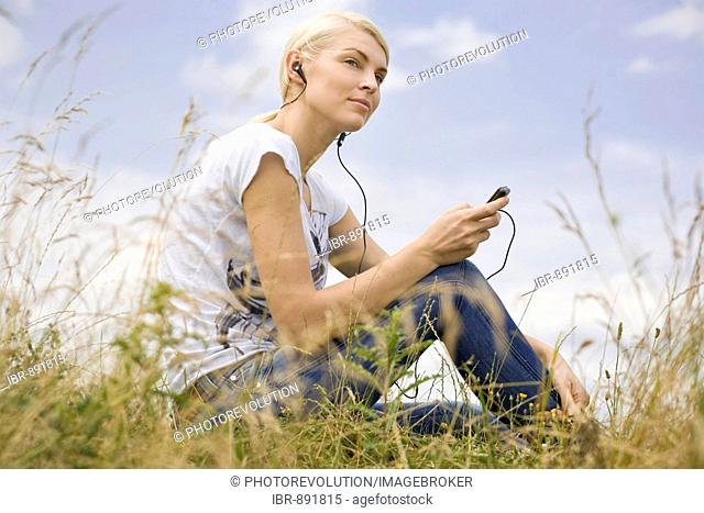 Smiling young blonde woman sitting in long grass and listening to music