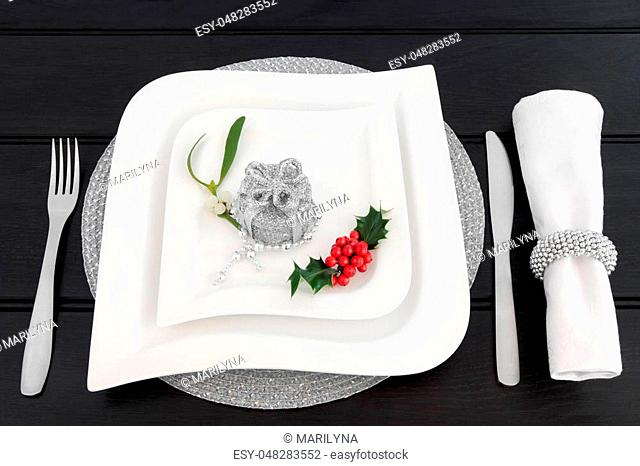 Christmas dinner table setting with white china plates, cutlery, linen serviette and ring, holly, mistletoe and silver gift box bauble decoration with bead...