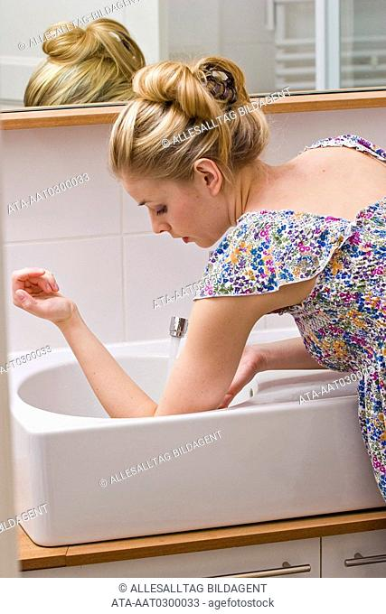 Woman cooling her elbow in the sink