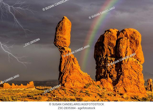 Balanced Rock Storm ANP - The golden light from the setting sun bathes Balanced Rock briefly after a heavy storm. A stormy sky and lightning can be seen in the...