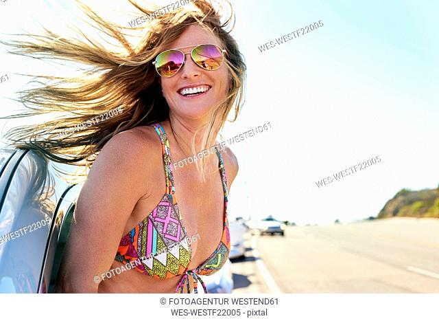 Happy young woman in bikini leaning out of car window